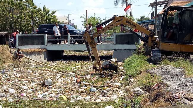 DIBERSIHKAN - Satu unit alat berat didatangkan Dinas PU Bina Marga dan SDA Pemkab Sidoarjo untuk membersihkan sampah yang menyumbat di Sungai Gedangan, Rabu (21/8/2019)
