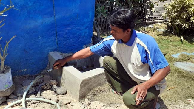 TES : Pelanggan PDAM saat mencoba menyedot air saluran PDAM Trunojoyo Sampang. (zyn)