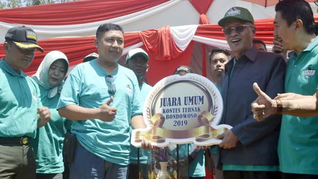 JUARA UMUM: Bupati KH. Salwa Arifin menyerahkan trofi juara umum Kontes Ternak Sapi Bondowoso 2019 pada Camat Tamanan Dwi Wahyudi. (ido)