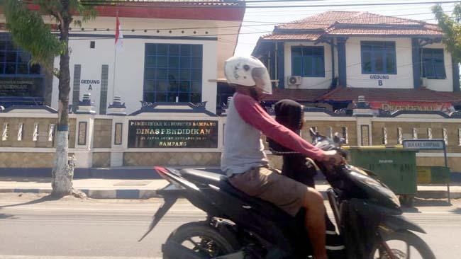 Pengendara saat melintas di depan Dinas Pendidikan Sampang. (zyn)