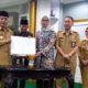 Ketua KPU Kabupaten Malang Anis Suhartini (Kanan berjilbab) bersama Bupati Malang HM Sanusi, menunjukkan hasil penandatanganan NPHD. (Ist)